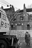 Woman watching demolition of Terraced houses 1977 London previously occupied by squatters. Some of the houses successfully resisted the demolition plans and were occupied until a second mass eviction... - Peter Arkell - 19-01-1977