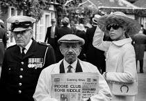 Royal Ascot races 1975 Newspaper seller, doorman women in hats arriving at Ascot racecourse, Berkshire - Peter Arkell - 20-06-1972