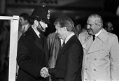 Jimmy Carter shanking hands with a policeman 1977 American president arriving at London Heathrow airport for a G7 meeting in the UK. Jim Callaghan introducing him to a line of VIPs - Peter Arkell - 05-05-1977