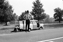 The People's Free Festival Windsor Park, 1973. Policeman make an arrest and police van on side of road - Peter Harrap - 25-08-1973