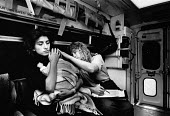 London 1989, Ambulance worker June Tuck tendingto sick baby in the arms of its mother in the back of an ambulance on the way to hospital - Melanie Friend - 19-04-1989