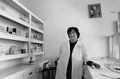Woman Pharmacist, Pharmacy, Himare, Albania 1990, a small seaside town. Portait of Enver Hoxha on the wall - Melanie Friend - 17-04-1990