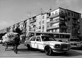 Mercedes Benz, Youth pulling a handcart, Tirana Albania 1996 housing block, cars and a bus - Melanie Friend - 03-05-1996