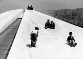Boys sliding down the Pyramid of Tirana, Albania 1996. Opened as the Enver Hoxha Museum, originally serving as a museum about the legacy of Enver Hoxha, the long time leader of Communist Albania. Afte... - Melanie Friend - 10-05-1996