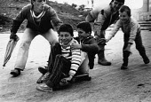 Children skateboarding, Berat, Albania, 1996. Pushing each other along on a homemade board - Melanie Friend - 03-05-1996