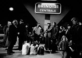 Albanian refugees, Brindisi Railway Station, Italy, 1991. Waiting for a train to transport them to a new life in northern Italy. Fleeing the collapse of communism in destitute Albania. - Melanie Friend - 14-03-1991