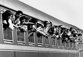 Albanian refugees Railway station, Brindisi, Italy 1991, waving from a train as they depart for a new life in northern Italy. Fleeing the collapse of communism in destitute Albania. - Melanie Friend - 15-03-1991