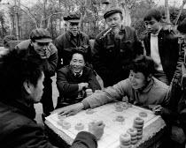 Men playing Xiangqi, park, Chengdu, Sichuan, China, 1986. The Xiangqi board game is also known as Chinese Chess. Sichuan Province - Melanie Friend - 20-03-1986