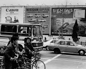 Beijing, China, 1986. Canon, Nissan and Siemens adverts, Cyclists waiting at traffic lights with cars and a bus with advertisments for computers and cars from Western and Japanese manufacturing compan... - Melanie Friend - 11-04-1986