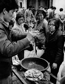 Trader selling fish in the market, Suzhou, China 1986. Weighing fish in front of women customers - Melanie Friend - 22-04-1986