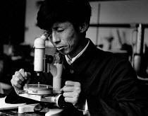 China, 1986. Lecturer using microscope, science laboratory, teachers college, Nanjing, Jiangsu - Melanie Friend - 27-04-1986