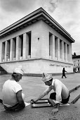 Bulgarian men 1992 wearing newspaper hats playing backgammon infront of the Georgi Dimitrov Mausoleum, Sofia, Bulgaria. Built in 1949, it was intended to contain the embalmed body of the first Communi... - Melanie Friend - 07-06-1992