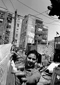 Roma woman hanging laundry, Stolipinovo, 1995, a deprived suburb of Plovdiv, which is inhabited by Roma and Bulgarian Turks. Plovdiv, Bulgaria - Melanie Friend - 28-05-1995