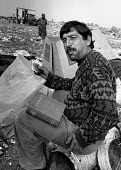 Roma scavenging the municipal rubbish dump, Plovdiv, 1995, Bulgaria. finding a copy of The Works of Lenin amoungst the landfill recycling refuse - Melanie Friend - 29-05-1995