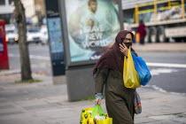 Shopper in mask and Brave New World Sky One advert, Watney Market, Stepney, East London. Film based on the Aldous Huxley groundbreaking 1932 novel, Brave New World which imagines a utopian society tha... - Jess Hurd - 15-10-2020