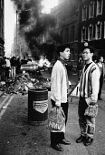 Poll Tax Riot, St. Martin's Lane, London 1990. Tourists looking bewildered by car on fire after shopping in Oxford Street HMV - Melanie Friend - 31-03-1990