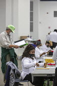 Detroit, USA-Absentee ballots, Presidential Election. Workers for the Detroit Department of Elections pre-process absentee ballots to prepare them for counting on election day. The man in the green ha... - Jim West - 02-11-2020