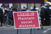 Pupils socialising, bus stop by Covid-19 Maintain Social Distance sign, Stratford Upon Avon, Warwickshire - John Harris - 10-11-2020