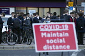 Pupils socialising, bus stop by Covid-19 Maintain Social Distance sign, Stratford Upon Avon, Warwickshire. Faces blurred - John Harris - 10-11-2020