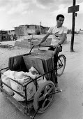 Gaza Strip, 1991. Recycling cardboard by three wheeled bicycle, Beach refugee camp, Palestine. Sacks of flower - Melanie Friend - 27-10-1991