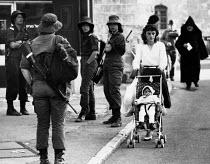 Jerusalem, 1984. Woman with pushchair passing Israeli women soldiers on patrol, Jersusalem, Israel - Melanie Friend - 29-03-1984