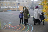 Parents bringing children to school wearing face masks, Lansbury Lawrence Primary School during Covid pandemic lockdown, Poplar, East London. - Jess Hurd - 27-11-2020