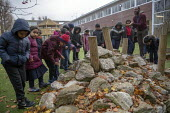 Teacher and pupils studying rock formations in the playground, Lansbury Lawrence Primary School during Covid pandemic lockdown, Poplar, East London. - Jess Hurd - 27-11-2020