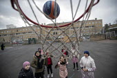 Shooting basketball hoops, breaktime in the playground, Lansbury Lawrence Primary School during Covid pandemic lockdown, Poplar, East London. - Jess Hurd - 27-11-2020