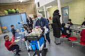 Staff wearing face masks and face visors. Dinner time, Lansbury Lawrence Primary School during Covid pandemic lockdown, Poplar, East London. - Jess Hurd - 27-11-2020