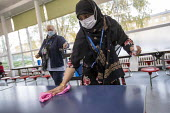 Dinner staff wearing face masks cleaning tables between each bubble. Lansbury Lawrence Primary School during Covid pandemic lockdown, Poplar, East London. - Jess Hurd - 27-11-2020