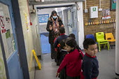 Staff wearing face masks. Bubble queuing at Dinner time, Lansbury Lawrence Primary School during Covid pandemic lockdown, Poplar, East London. - Jess Hurd - 27-11-2020
