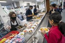 Dinner staff serving dinner wearing face masks, Lansbury Lawrence Primary School during Covid pandemic lockdown, Poplar, East London. - Jess Hurd - 27-11-2020
