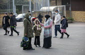 Home time, parents collecting their children, Lansbury Lawrence Primary School during Covid pandemic lockdown, Poplar, East London. - Jess Hurd - 27-11-2020