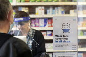 Pharmacist wearing face shield serving a customer, a protective perspex screen is across the counter, Pharmacy, Bristol - Paul Box - 05-12-2020