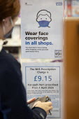 Sign requiring customers to wear a face covering in all shops, Pharmacy, Bristol with a protective perspex screen across the counter - Paul Box - 05-12-2020