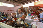 Teotitlan del Valle, Oaxaca, Mexico: Cook, small restaurant, Comedor Jaguar serving Red Chile Enchiladas. Rural women in the Tlacolula Valley benefit from a microfinance loan program run by the nonpro... - Jim West - 30-01-2020