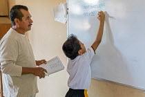 Brisas de Zicatela, Oaxaca, Mexico: Pupil solving an equation. A teacher watching, maths class, Escuela Primaria Tierra y Liberdad primary school - Jim West - 05-02-2020