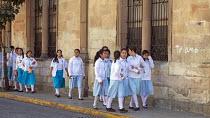 Oaxaca, Mexico: School girls waliking along a street. I love you graffiti on the wall - Jim West - 02-02-2020
