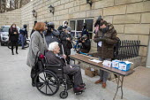 Lansing, Michigan USA. Electoral College Meeting. Elector Mike Kerwin (in wheelchair) arriving at the Michigan state capitol to cast his vote for Joe Biden. Kerwin, a long-time UAW activist, is pushed... - Jim West - 14-12-2020