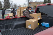 Detroit, USA Muslims and Christians delivering food aid- Michigan Muslim Community Council and St. Hedwig Catholic Church delivering food boxes and Christmas packages to families in need. Volunteers p... - Jim West - 19-12-2020