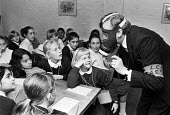 Age Exchange 1990. Air Raid Warden in gas mask talking to pupils about World War Two and The Blitz. School children visiting Age Exchange, Greenwich, London - Peter Arkell - 20-01-1990