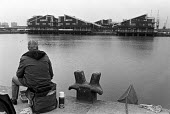 Man fishing, West India Dock, East London, 1986 looking across to the new development as it gets underway - Peter Arkell - 10-09-1986