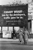 Canary Wharf Jam For The Developers, Traffic Jams For Us. Women walking past an Advertisement questioning the value of the development of the docklands area in East London to the residents of the Isle... - Peter Arkell - 09-03-1987