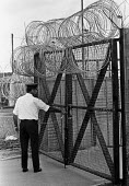 Prison Officer locking the gate, HMP Rollestone Prison, Wiltshire 1987. The temporary prison was used to relieve overcrowding in civilian prisons - Peter Arkell - 10-08-1987