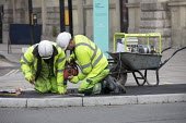 Workers repairing pavement during Covid pandemic lockdown, Piccadily, London. Working in close proximity outdoors - Jess Hurd - 03-03-2021