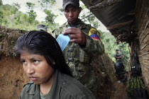 24-06-2010 - A woman member of the FARC guerilla has her hair combed by her boyfriend, hiden behind a wooden house to evade helicopters searches, on Thursday, June 24, 2010. © Boris Heger