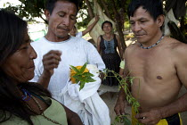 20-01-2011 - An internally displaced indigenous men who just came back from a weeks hunting, show their family members traditional medicinal herbs they have found. San Jose del Guaviare, Colombia. © Boris Heger