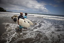 13-08-2011 - Young surf champion PJ walking into the waves with his friend. Choco, Colombia. © Boris Heger