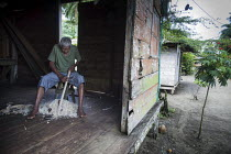 15-08-2011 - A man working on a piece of wood in his home. Choco, Colombia. © Boris Heger