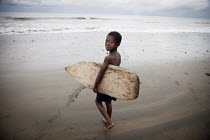14-08-2011 - A young surfer heading to the water with a surfboard his older brother made for him from a balsa tree in the jungle. Choco, Colombia. © Boris Heger